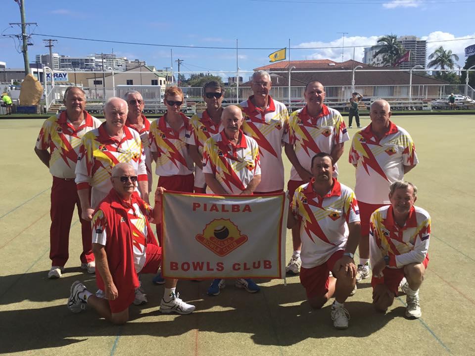Members of Pialba Bowls Club holding club banner